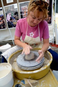 An artist is working a potters wheel and making a bowl at the Leaf and String Festival, Galax, Va.