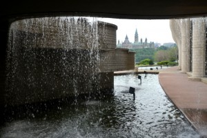 Looking through a window of glass in the Museum of Civilization and downtown Ottawa in the background.