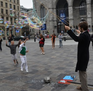 Youngsters entertained by a bubble making street performer in the plaza at Notre-Dame Basilica.