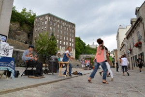 Visitors enjoy an impromptu dance to tunes provided by a street performer in Old Quebec.