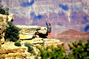 A park visitor climbs out on a ledge and takes a video of the canyon over her shoulder.