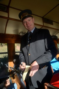 Conductor in authentic uniforms from the past, punch tickets of train riders.