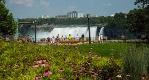 Tourists along the walkway above the Niagara Falls looking toward the city of Niagara Falls in the background.