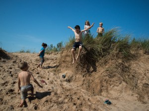 Youngsters line up to take their turn jumping off the dunes into soft sand at least eight inches deep.