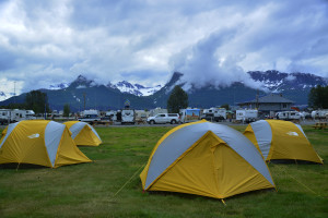 Tents are lined up for campers at Valdez with snow covered mountains in background.