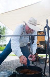 The chuck wagon cook stirs the beans and offers samples to bystanders.